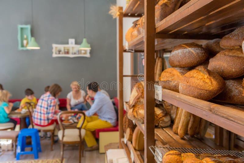 Bröd på en hylla med folk som sitter på tabeller royaltyfri fotografi