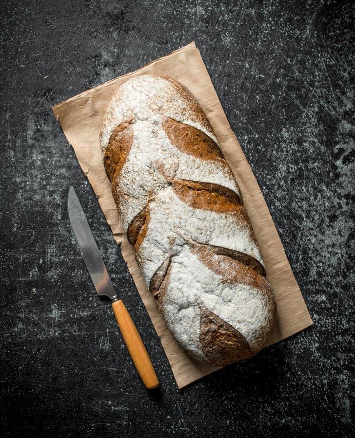 Bröd på papper med en kniv royaltyfri fotografi