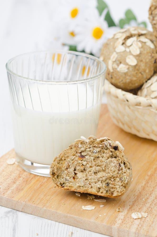 Bröd rullar wholemeal med oatflingor, och ett exponeringsglas av mjölkar royaltyfria bilder