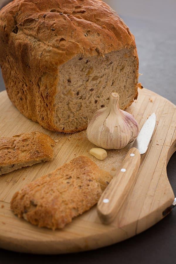 bröd skivad kniv med vitlök och att salta på ett trä royaltyfria bilder