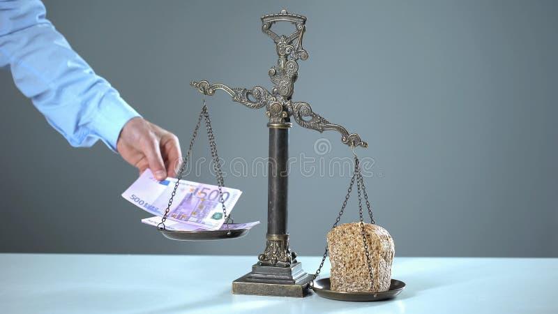 Bröd väger mer än euroet på våg, armodbegreppet, fattigt folk mer än rich royaltyfria bilder