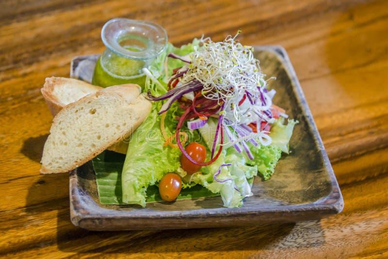 Bröd, vagatable gräsplan och tomatsallad i plade på trätabellen royaltyfria bilder