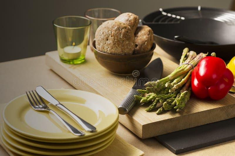 Bröd, Veggies, kniv, exponeringsglas och plattor på tabellen fotografering för bildbyråer