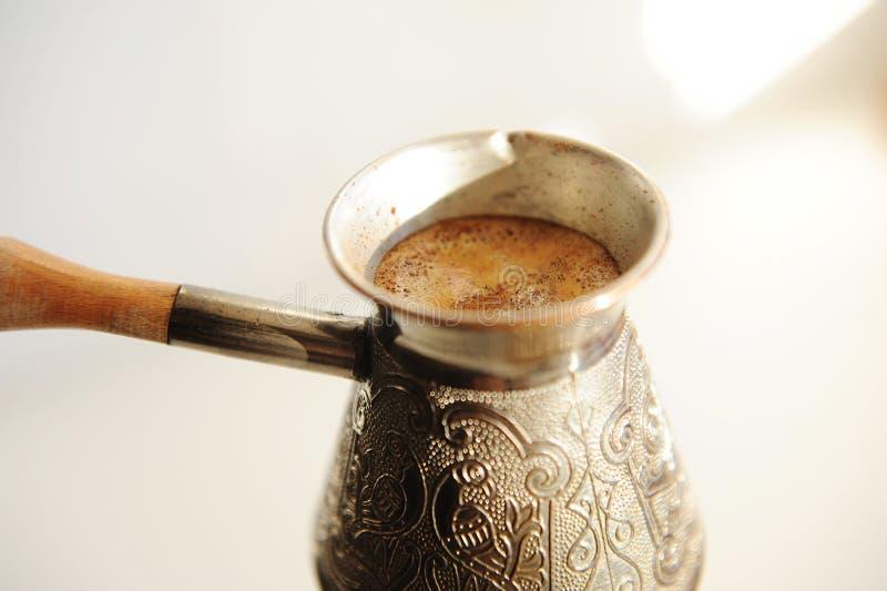 Brödande turkiskt kaffe i koppar, cezve nära Vit bakgrund royaltyfria bilder