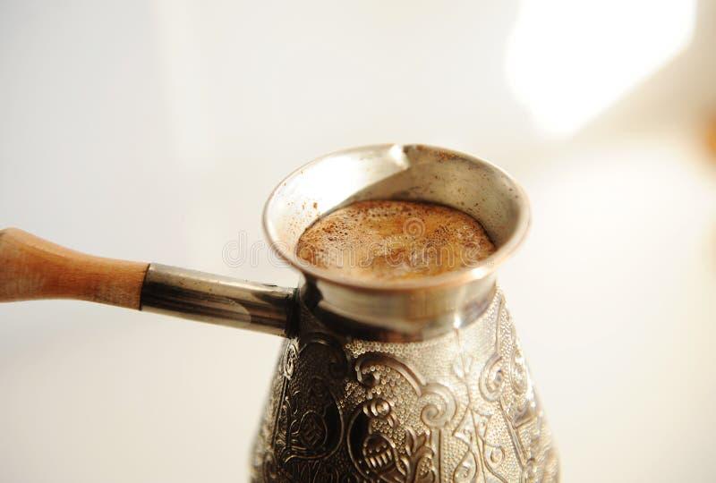 Brödande turkiskt kaffe i koppar, cezve nära Vit bakgrund royaltyfri bild