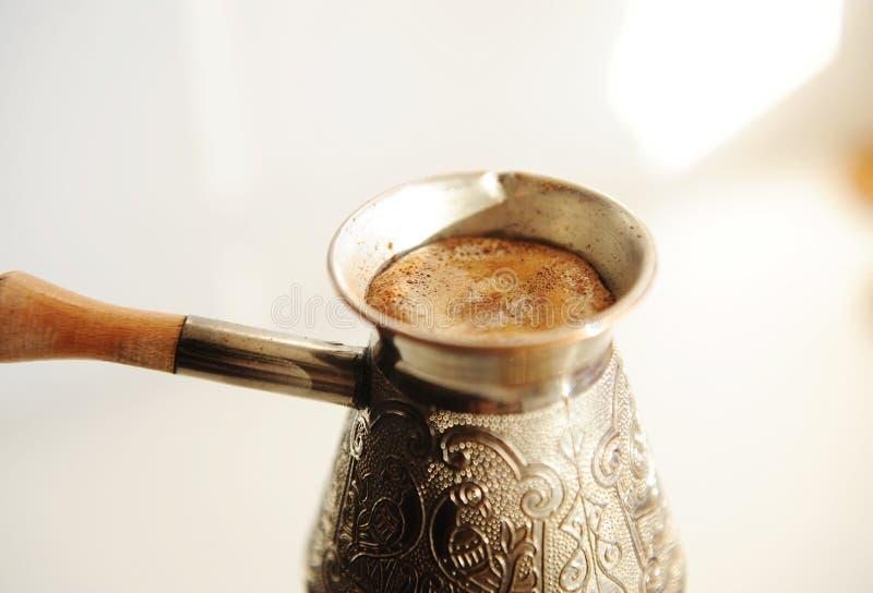 Brödande turkiskt kaffe i koppar, cezve nära Vit bakgrund arkivfoton