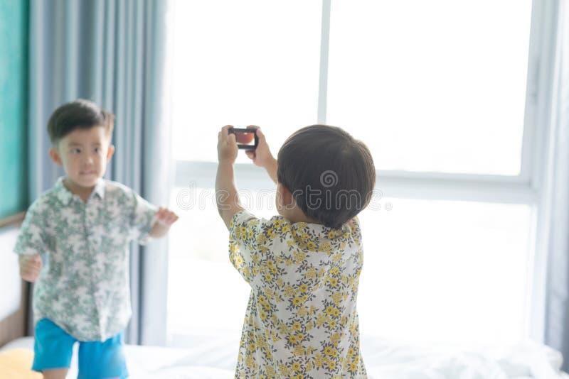 Bröder tar en bild morgonen på sängen arkivbild