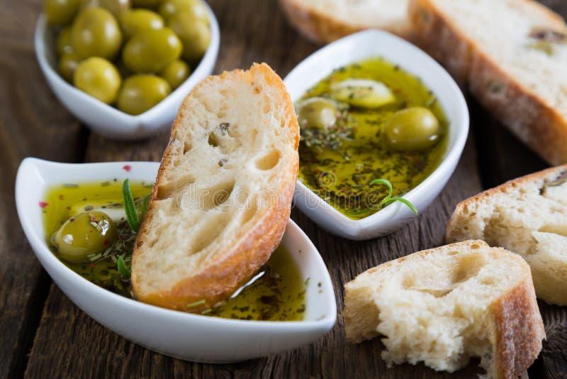 Brödet doppade i olivolja med örter och kryddor royaltyfri fotografi