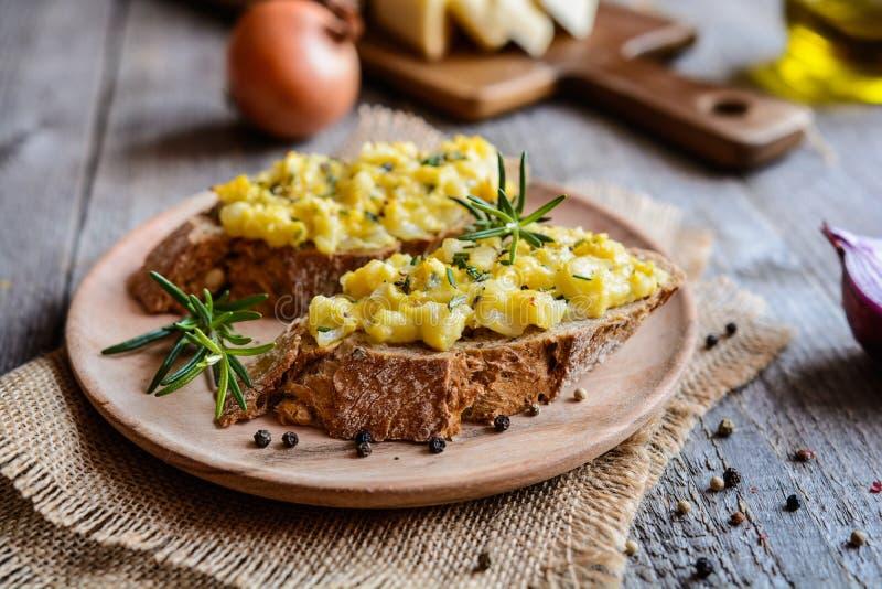 Brödskivor för helt mål med den förvanskade ägg, ost och löken arkivfoto