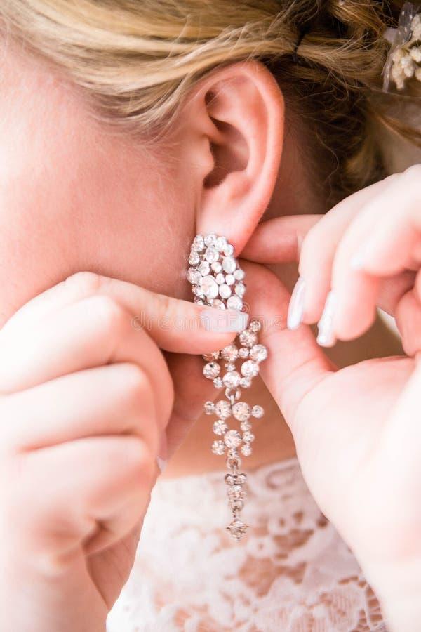 Bröllopörhängen på en kvinnlig hand, tar hon örhängena royaltyfria bilder