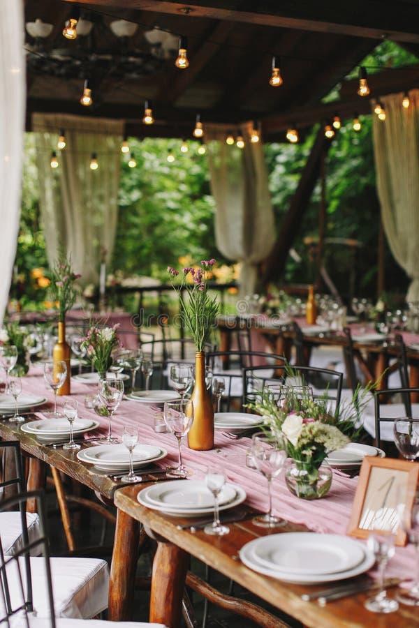 bröllop _ Den festliga tabellen för gäster som dekoreras med en sammansättning av vit och rosa färgblommor och grönska fotografering för bildbyråer