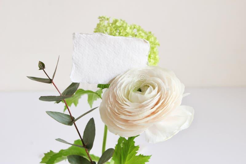 Bröllop- eller födelsedagmodellplats med den blom- buketten av den persiska smörblomman, Ranunculusblomman och eukalyptussidor me arkivfoton