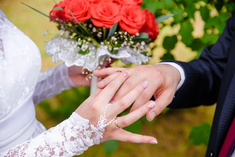 bröllop för brudceremoniblomma Bruden sätter cirkeln på groom&en x27; s-finger arkivbild