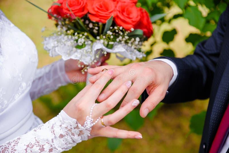 bröllop för brudceremoniblomma Bruden sätter cirkeln på groom&en x27; s-finger royaltyfria foton