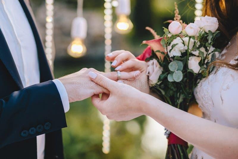 bröllop för brudceremoniblomma Bruden sätter på en vigselring till brudgummen på en bakgrund av ljusa kulor som rymmer en bukett  arkivbild