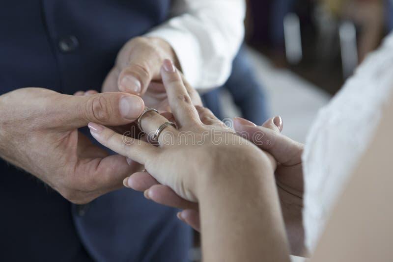 bröllop för brudceremoniblomma Brudgum Giving Wedding Ring To hans brid royaltyfri bild