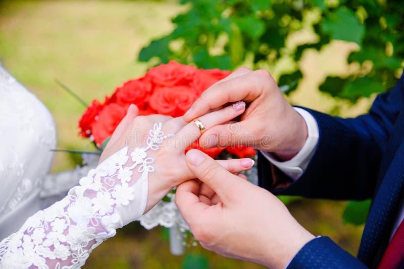 bröllop för brudceremoniblomma Brudgummen sätter cirkeln på bride&en x27; s-finger royaltyfri bild