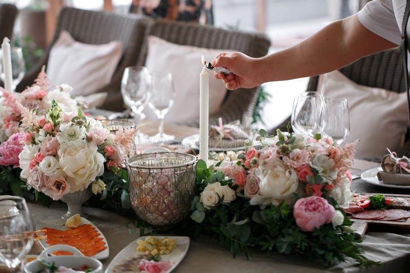 bröllop för tappning för klädpardag lyckligt uppassaren tänder en stearinljus Romantisk matställe arkivbild