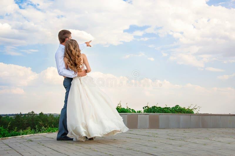 bröllop för tappning för klädpardag lyckligt Härlig brud i armarna av brudgummen på himmelbakgrund royaltyfri foto