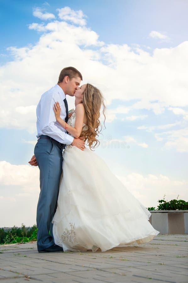 bröllop för tappning för klädpardag lyckligt Härlig brud i armarna av brudgummen på himmelbakgrund royaltyfria bilder