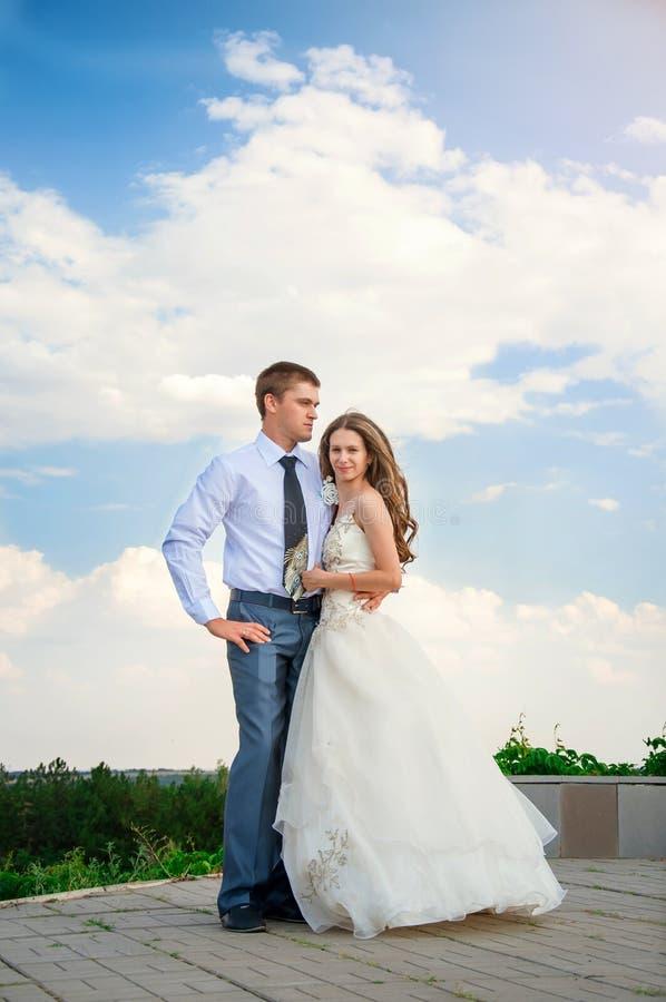 bröllop för tappning för klädpardag lyckligt Härlig brud i armarna av brudgummen på himmelbakgrund royaltyfri bild