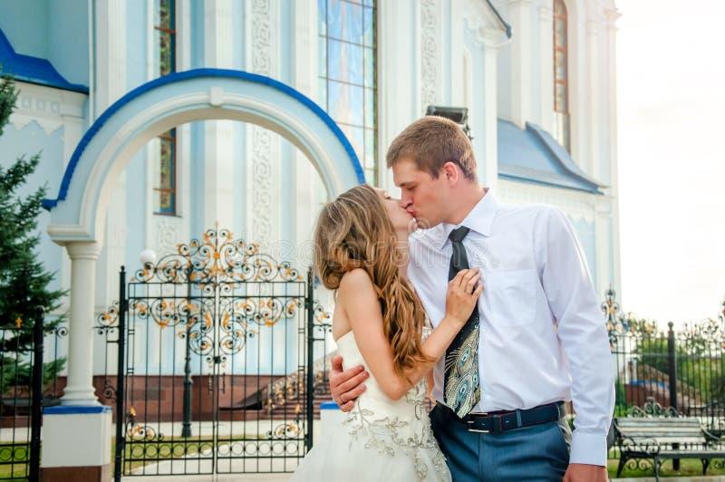 bröllop för tappning för klädpardag lyckligt lyckligt kyssa för par Det lyckliga ung flickainnehav hänger lös på en vitbakgrund royaltyfri foto