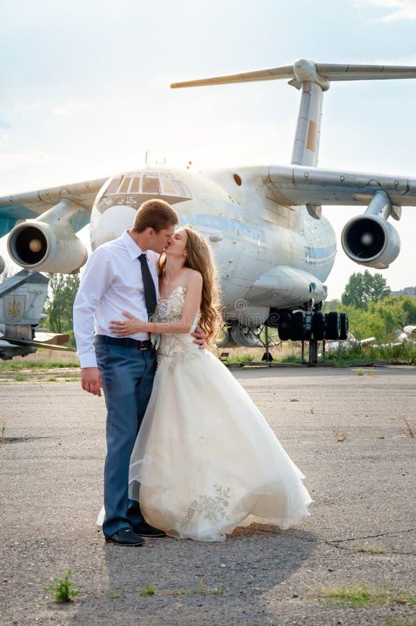 bröllop för tappning för klädpardag lyckligt Lyckliga kyssande par på bakgrunden av flygplanet arkivfoto