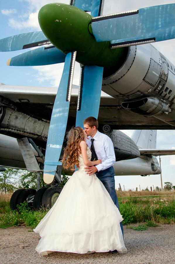 bröllop för tappning för klädpardag lyckligt Lyckliga kyssande par på bakgrunden av flygplanet arkivbild