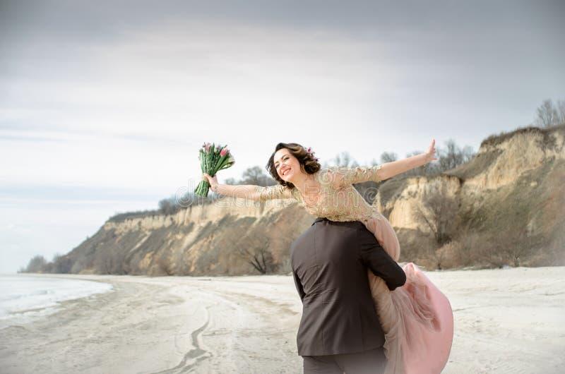 bröllop Gifta sig vid ishavet Barnet kopplar ihop förälskat, brudgummen och bruden i bröllopsklänning på sjösidan förbunden föräl royaltyfri bild