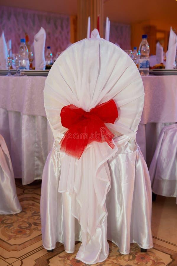 Bröllop Hall Decoration Stol i ett fall med det röda bandet royaltyfri fotografi