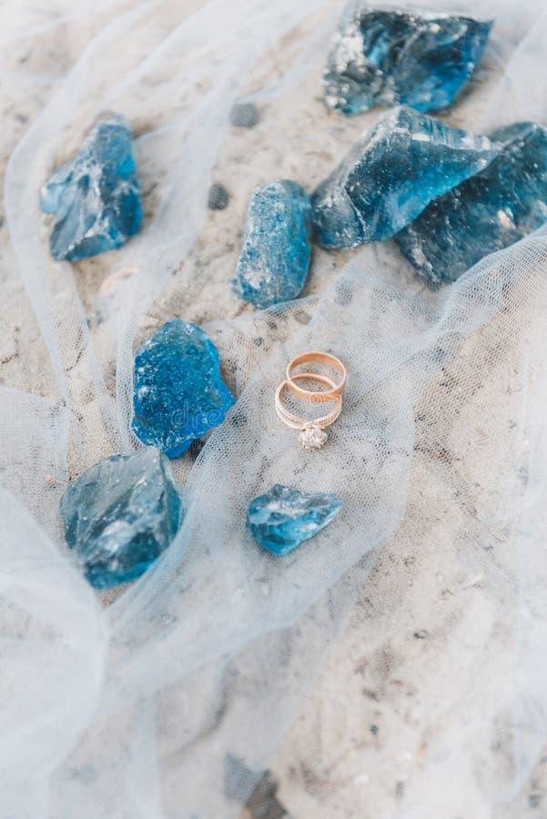 Bröllop och förlovningsringar på ett rent tyg på en strand med dekorativa blåa stenar royaltyfri fotografi