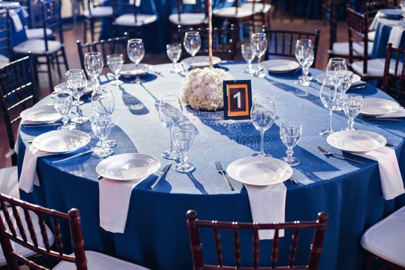 bröllop _ Stolarna och den runda tabellen för gäster som tjänas som med bestick och lerkärl och täckas med en blått fotografering för bildbyråer