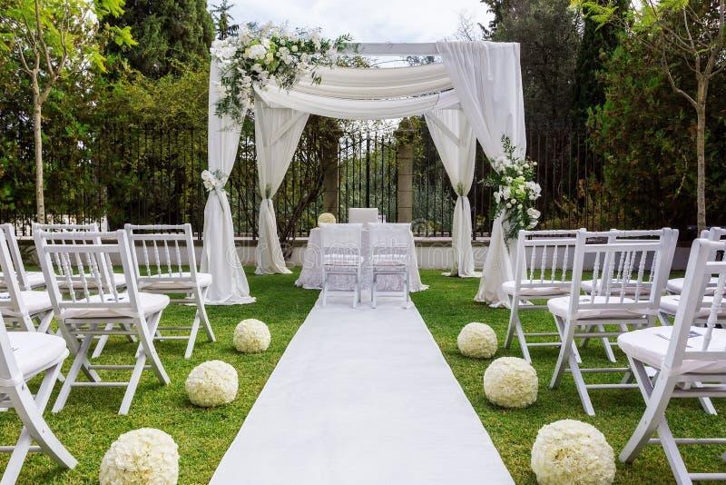 Bröllopbana och garneringar för nygifta personer I natur i trädgård arkivfoto