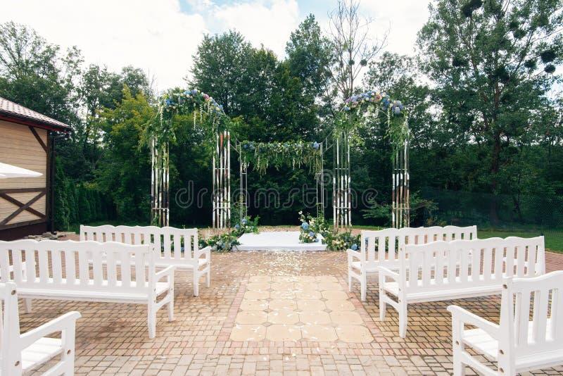 Bröllopbana och garneringar för nygifta personer I natur i trädgården royaltyfria foton