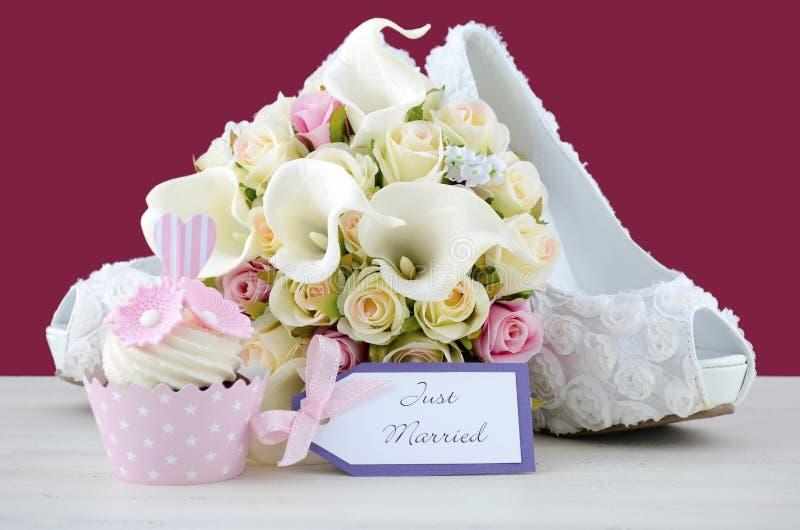 Bröllopbegreppsmuffin och sko på marsalabakgrund arkivbilder