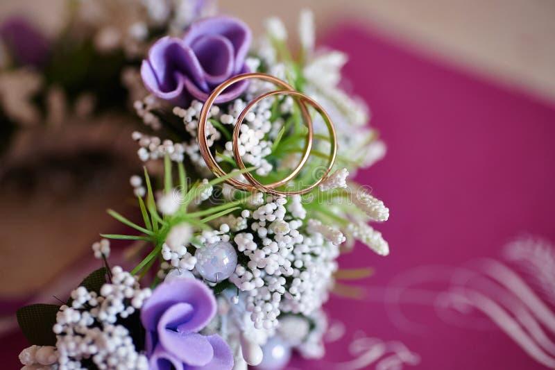 Bröllopboutonniere av blommor och guld- cirklar royaltyfria bilder