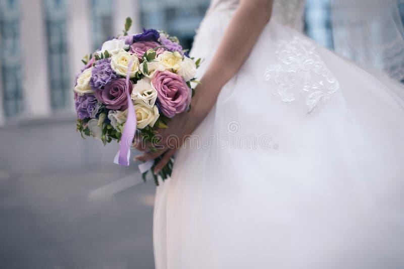 Bröllopbukett av purpurfärgade och vita blommor i händerna för brud` s royaltyfri foto