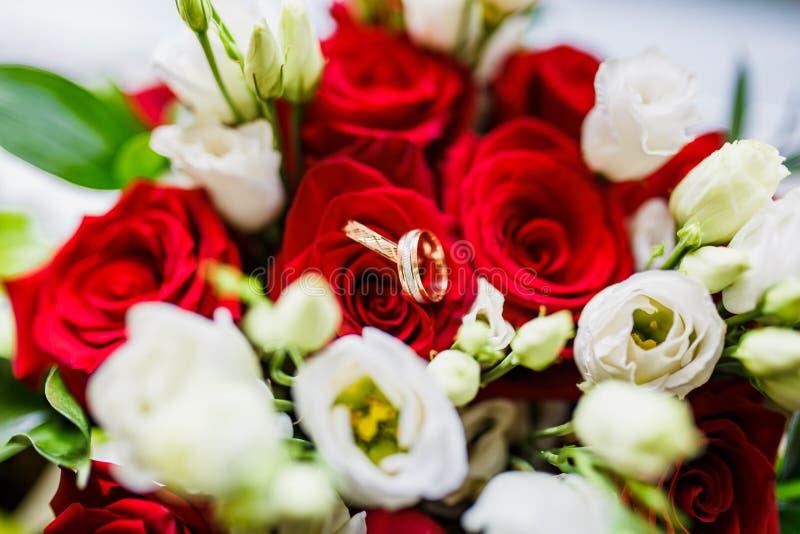 Bröllopbukett av röda och vita rosor och guld- vigselringar arkivbild