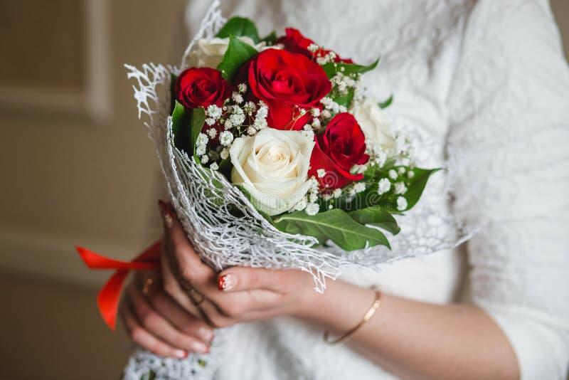 Bröllopbukett av röda rosor i bruds händer med härlig manikyrnärbild arkivbild