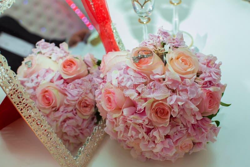 Bröllopbukett av rosa rosor och vigselringar på en trätabell kopiera avstånd Begreppet av ett bröllop, parti, förälskelse och arkivfoto