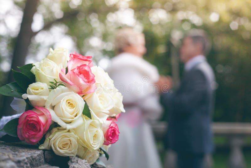 Bröllopbukett av vita och scharlakansröda rosor på bakgrunden arkivfoto
