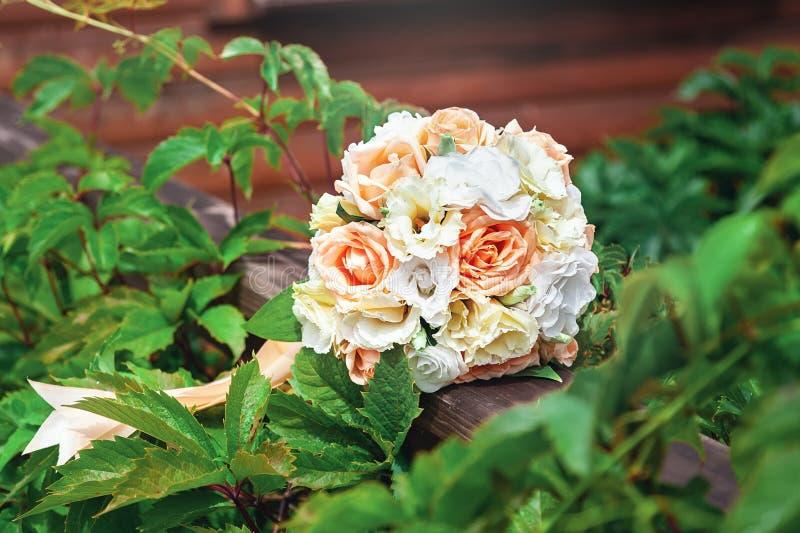 Bröllopbukett av vitt, guling och persikarosor mot gröna sidor royaltyfri fotografi