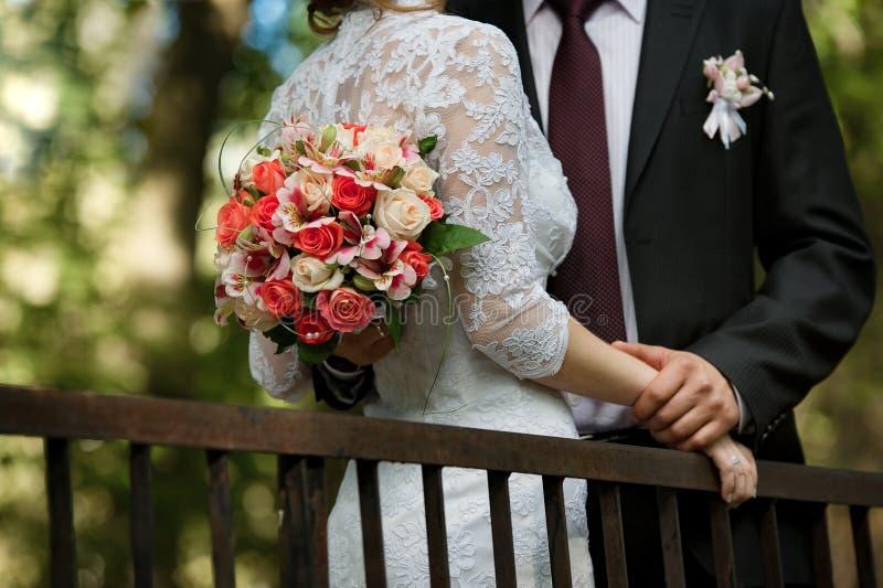 Bröllopbukett i händer av brudgummen i bröllopdag Brud- par royaltyfria bilder