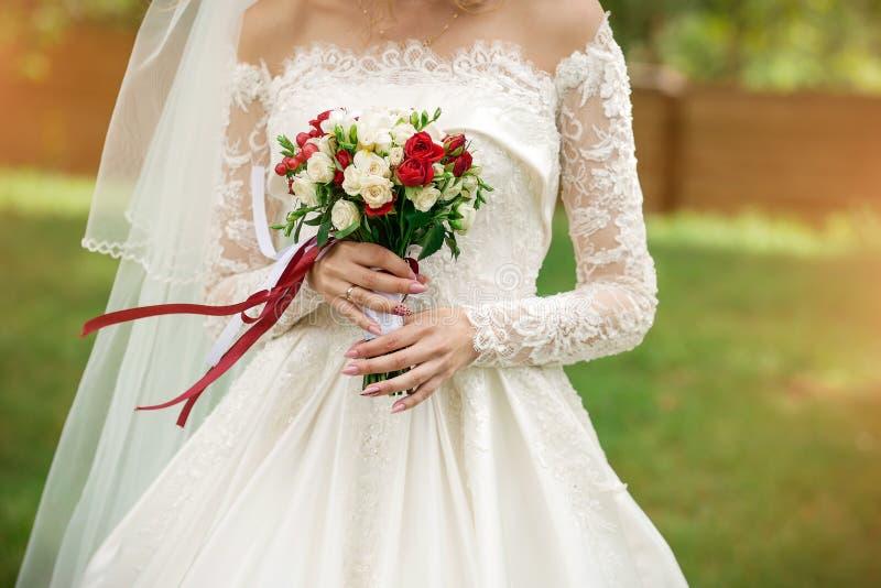 Bröllopbukett i händerna av brudnärbilden arkivbilder