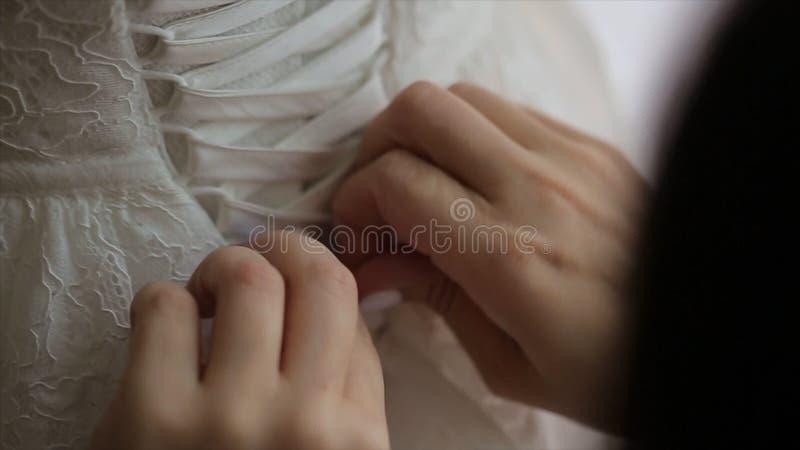 Bröllopbukett in i korg förnämsta brudtärna som hjälper bruden med hennes klänning brud`en s snör åt upp klänningen Brudtärna som fotografering för bildbyråer