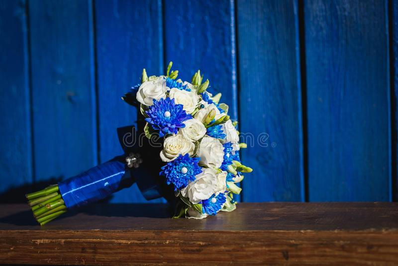 Br?llopbukett med bl?a och vita blommor p? en bl? bakgrund royaltyfri bild