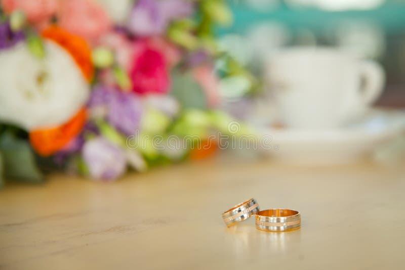 Bröllopbukett och kaffe med vigselringarna på tabellen fotografering för bildbyråer