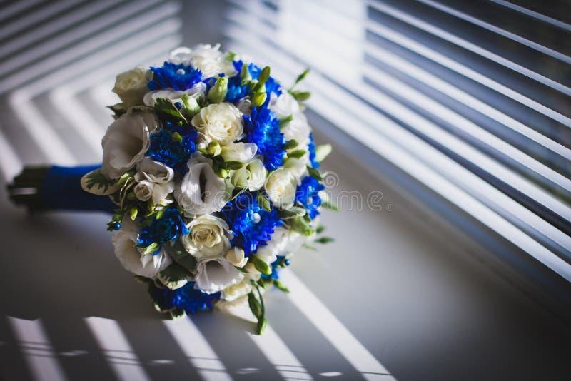 Br?llopbukett p? f?nstret med rullgardiner attributen av brudgummen par som nytt att gifta sig arkivbild