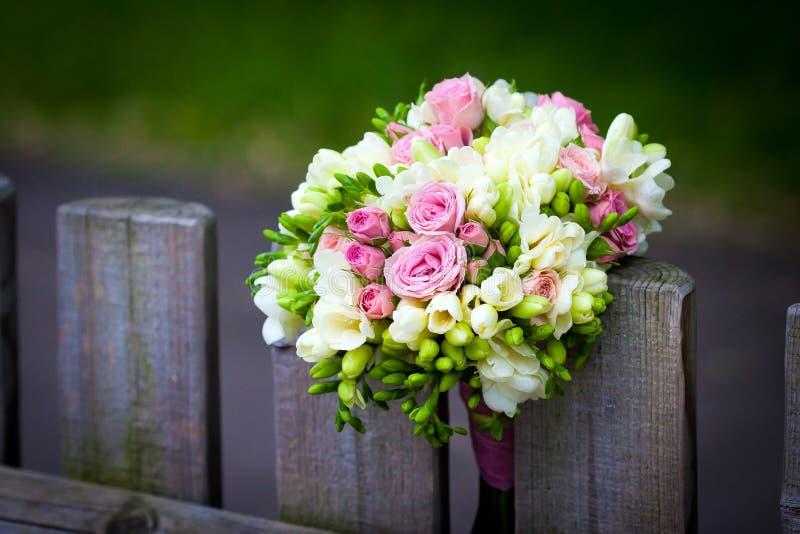 Bröllopbukett på lantligt landsstaket royaltyfri foto