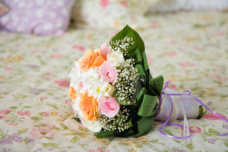 Bröllopbukett på säng royaltyfria foton